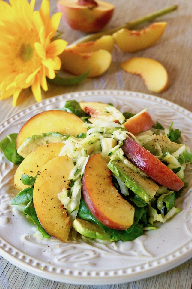 Peach and Avocado Salad with Zucchini on a white plate with a sunflower.