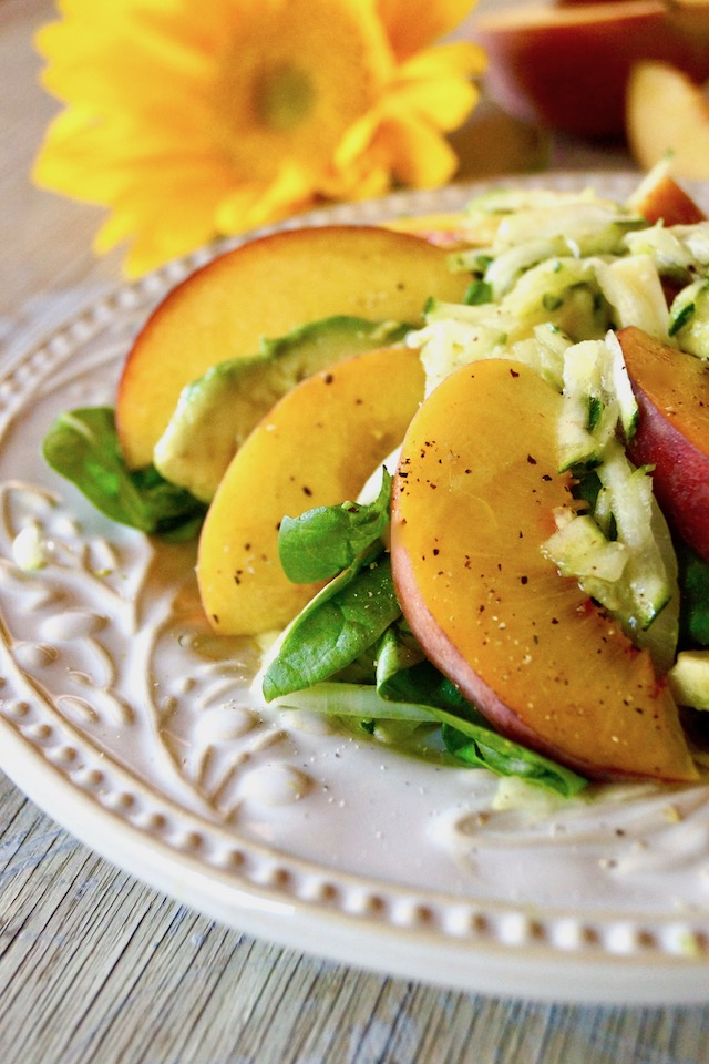 Close up of Peach and Avocado Salad with Zucchini on a white plate.