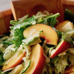 Summer Zucchini Peach Avocado Salad in a wooden serving bowl.