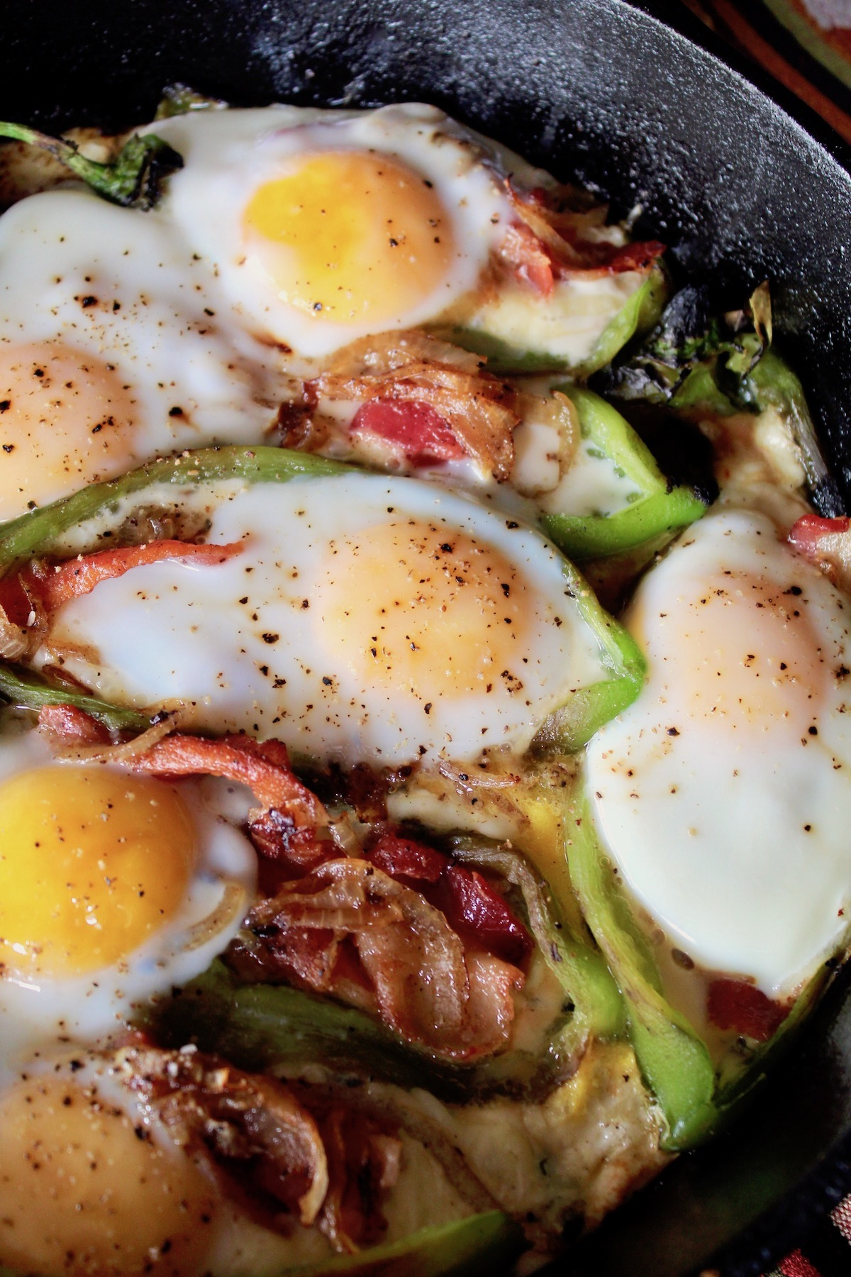 eggs on green chiles in cast iron skillet with bacon