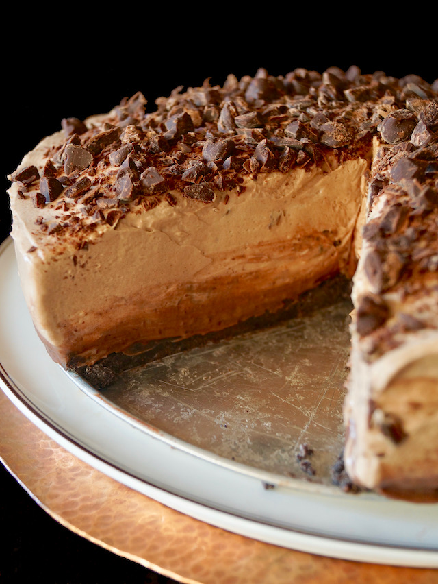 No-Bake Espresso Cheesecake with Ganache on cake stand with one large piece removed