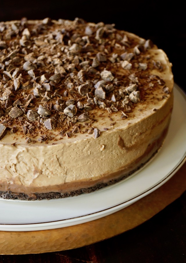 No-Bake Espresso Cheesecake with Ganache on a white cake stand.