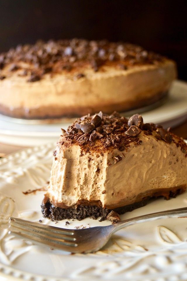 Slice of No-Bake Espresso Cheesecake with Ganache with one bite missing on cream plate