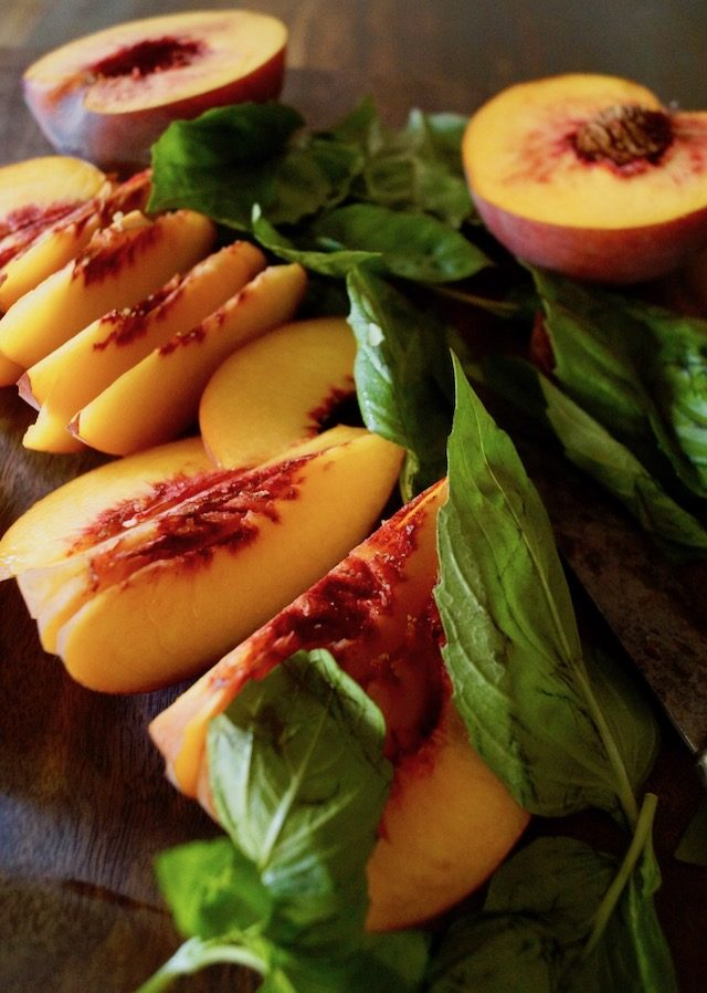 slices of peaches and basil leaves on a dark wood cutting board