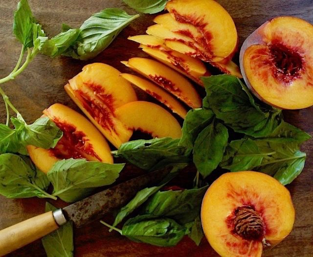 slices of peaches and basil leaves on a dark wood cutting board with knife