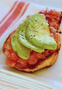 Toast with breakfast tomatoes and avocado slices on a white plate.