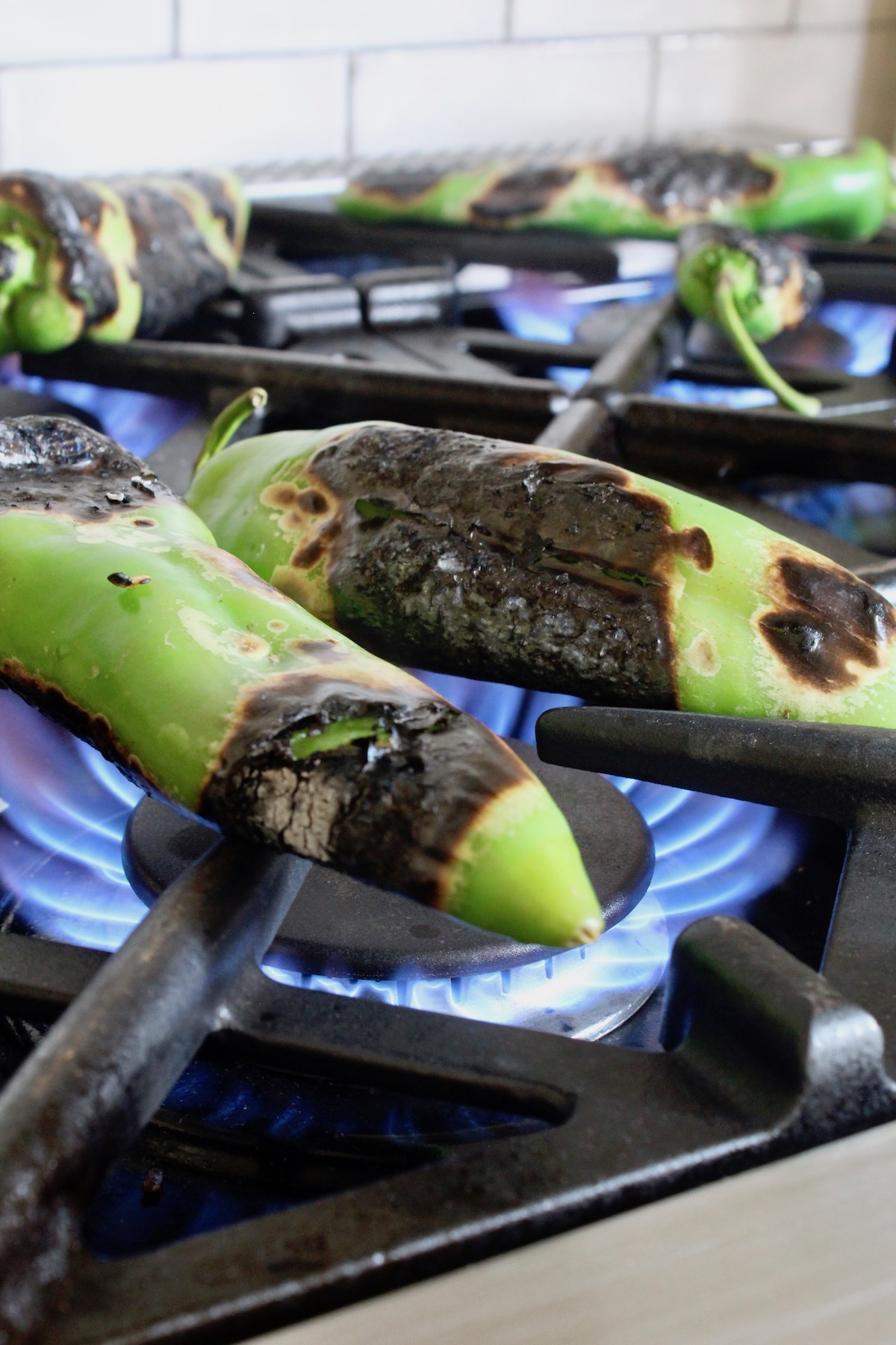 hatch chiles on burners of stove being roasted