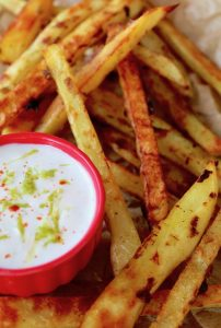 small red bowl with yogurt lime dip surround by French fries