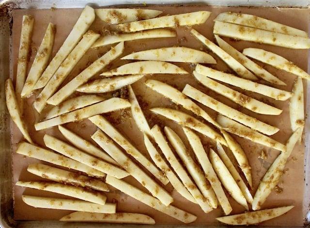 raw potato sticks on a sheet pan with curry paste