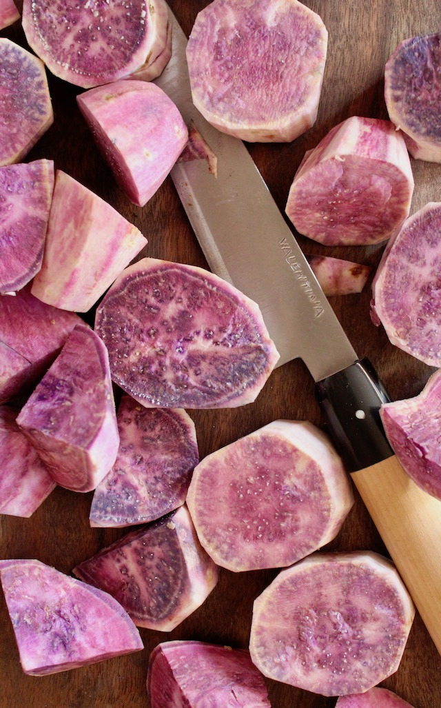raw hawaiian purple potatoes cut into chunks with knife