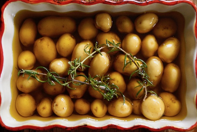 Baby Confit Potatoes in olive oil with rosemary in baking dish