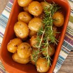 small Dutch Yellow potatoes in a terracotta dish with rosemary sprigs