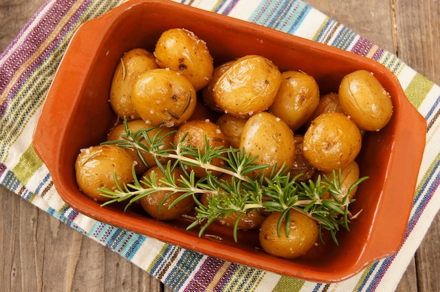 Rosemary Confit Potatoes in a teracotta dish with rosemary sprigs