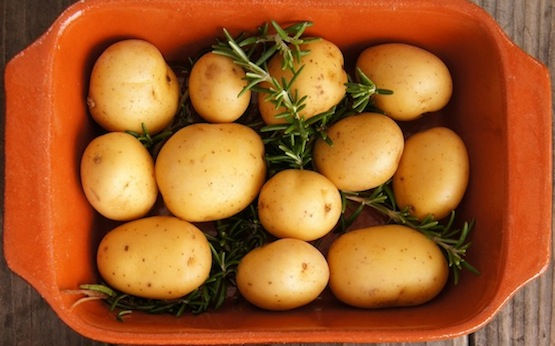 Small potatoes in a teracotta dish with rosemary sprigs