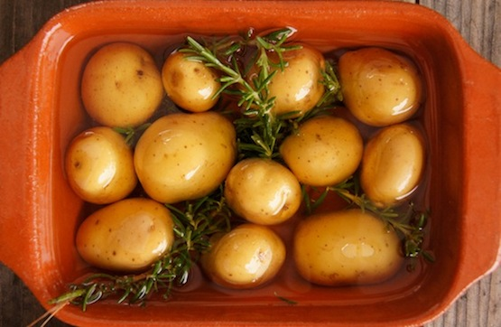 Rosemary Confit Potatoes in a teracotta dish with rosemary sprigs and oil.
