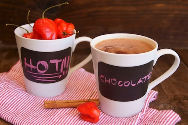 Spicy Mayan Hot Chocolate in a mug, with another mug full of red savina habanero peppers.