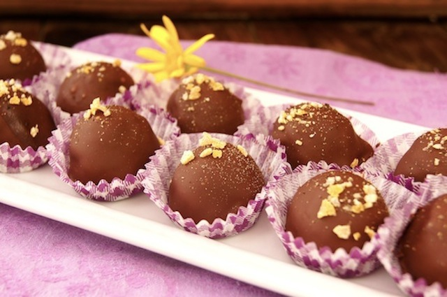 Lemon Pepper Chocolate Truffles on a white platter with a yellow daisy