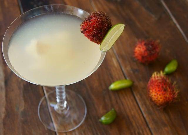 Rambutan Martini, a Rambutini, in a martini glass with fresh rambutan and finger limes.