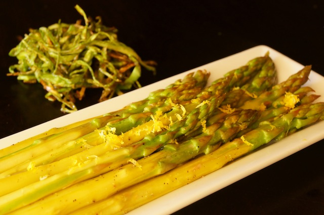Asparagus on a white rectangular dish and s and Crispy Asparagus Garnish behind it