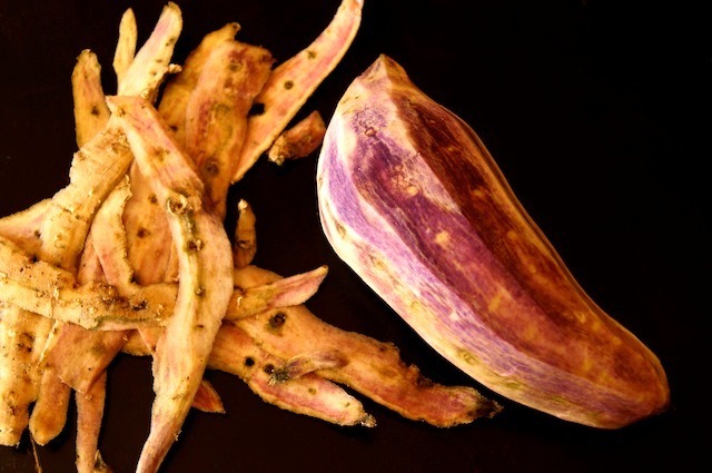 one peeled Okinawan Purple Sweet Potato with peels next to it on black background