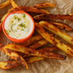 Curry French Fries on parchment with orange bowl filled with coconut lime dip