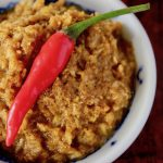 curry paste in small white bowl with red pepper