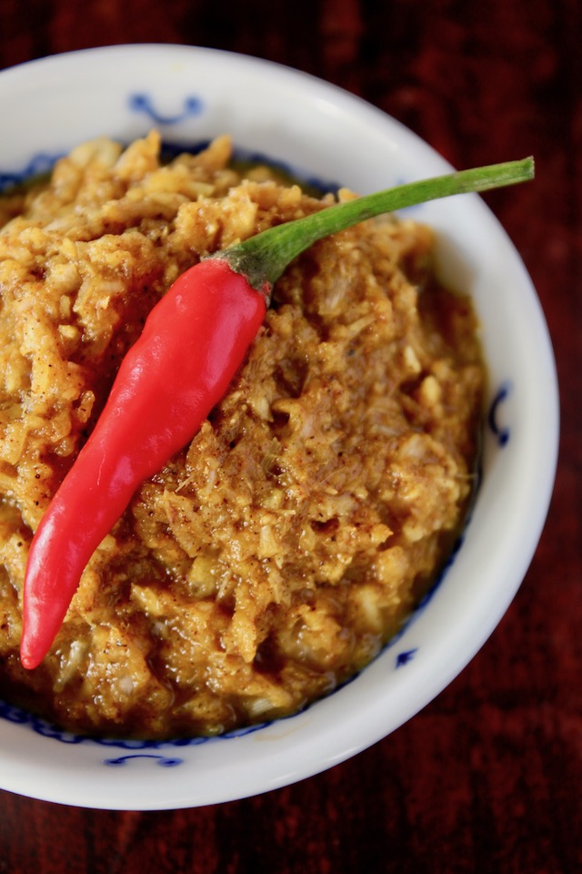 yellow curry paste in a white bowl with tiny red pepper on top