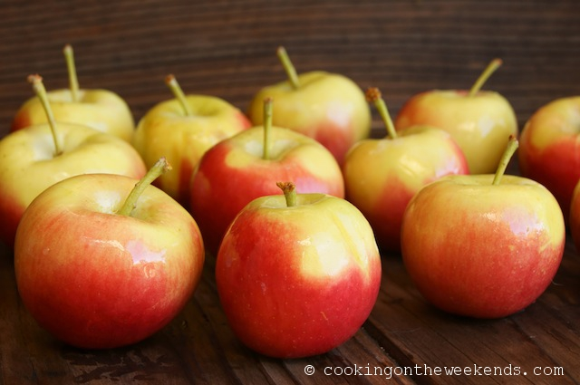Several shiny Crimson Gold Apples on a wooden surface.