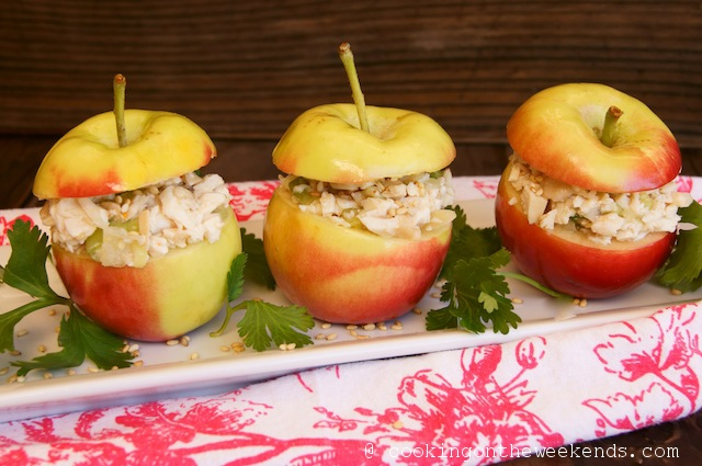 3 Crimson Gold Apples filled with Sesame Apple Chicken Salad on a white narrow plate with a red and white floral, cloth napkin.
