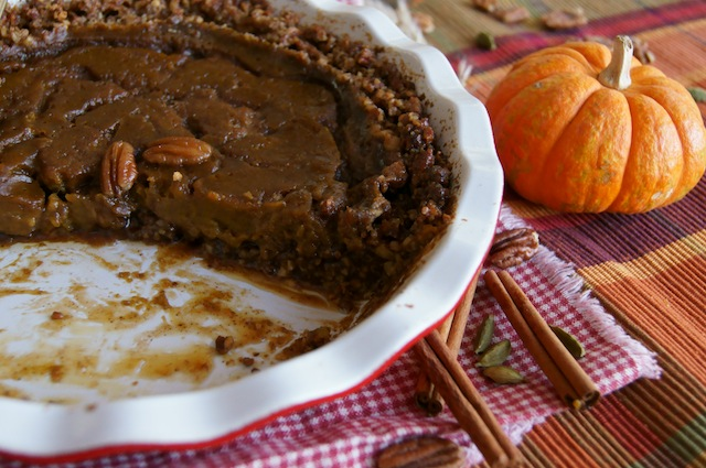 Pecan Crusted Salted Spiced Caramel Pumpkin-Pie with a few slices removed.
