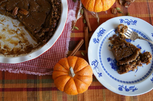 One slice of Pecan Crusted Caramel Pumpkin Pie on a blue and white plate with the remaining pie next to it.