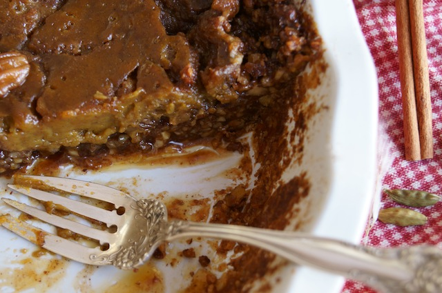 Pecan Crusted Salted Spiced Caramel Pumpkin Pie with a slice removed and a silver fork.