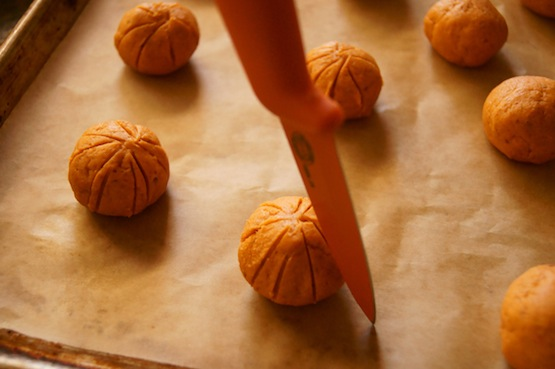Balls of Pumpkin Almond Cookie dough on parchment being shaped inot pumpkins with an orange paring knife.