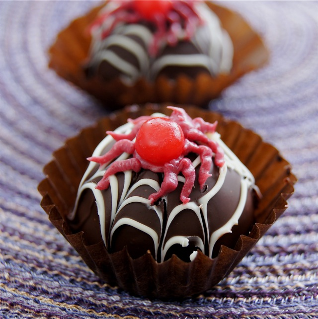 Two Spooky Spider Chocolate Truffles on a purple placemat.