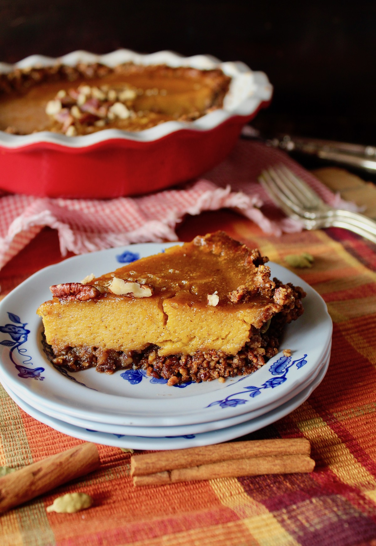 one slice of pecan crusted pumpkin caramel pie on a blue and white plate