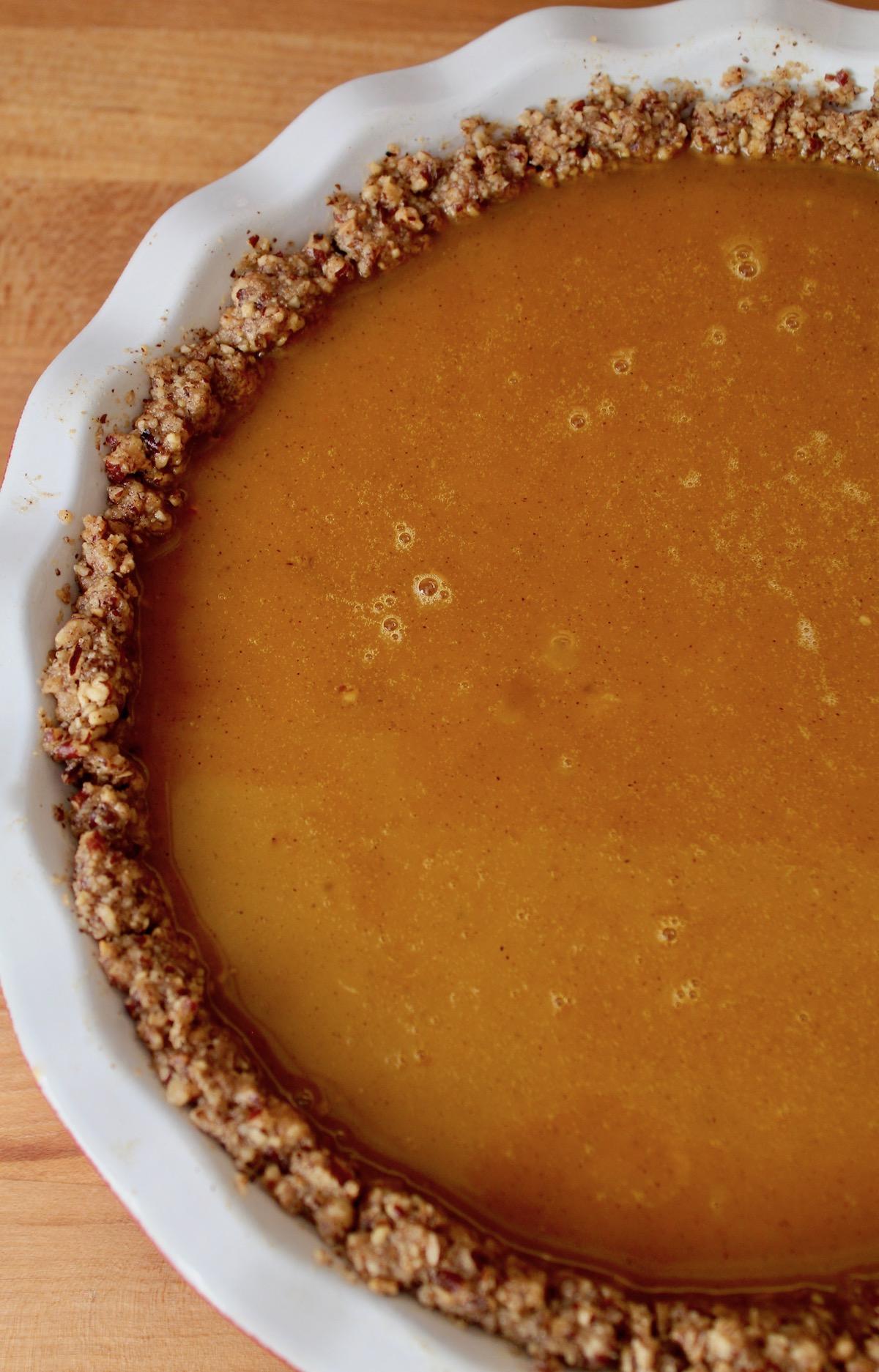 unbaked pumpkin pie in white pie plate