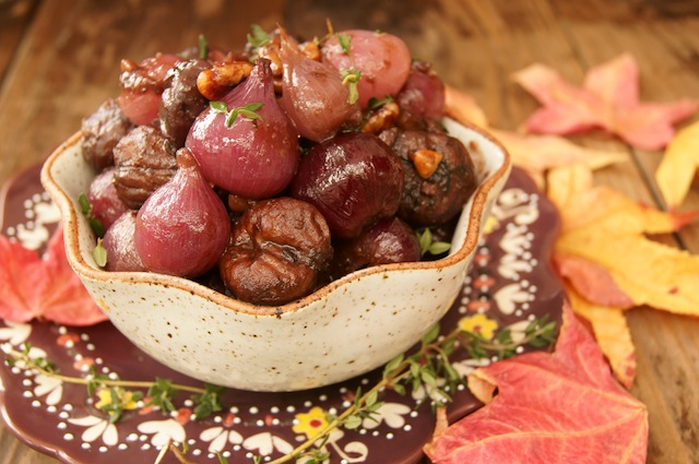 Braised Chestnuts and Pearl Onions in a pretty cream colored bowl with fall leaves around it