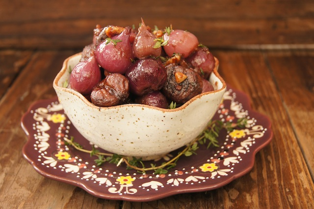 Red Wine Braised Chestnuts and Pearl Onions in pretty cream colored bowl on a burgandy plate with fresh thyme leaf