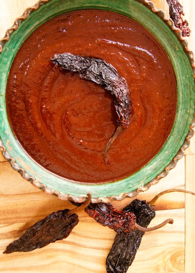 Red Ancho Chile Enchilada Sauce is thick and creamy in a green bowl with a dried chile