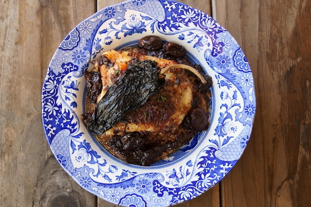 Chile-Red Wine-Grape Roasted Chicken with a dried Ancho chile on top in a blue bowl