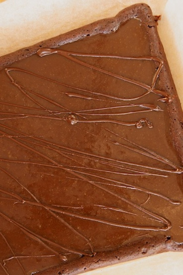 Gluten-Free Caramel Brownies with Espresso before its cut, in a square, with chocolate drizzled on top.