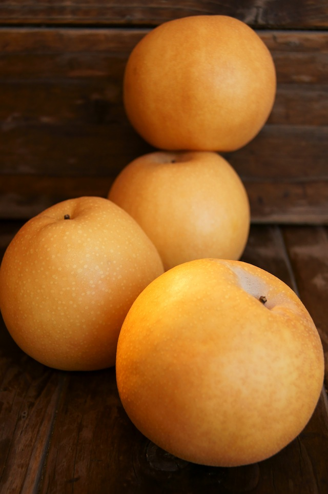 Korean Pears piled on top of each other on wood background