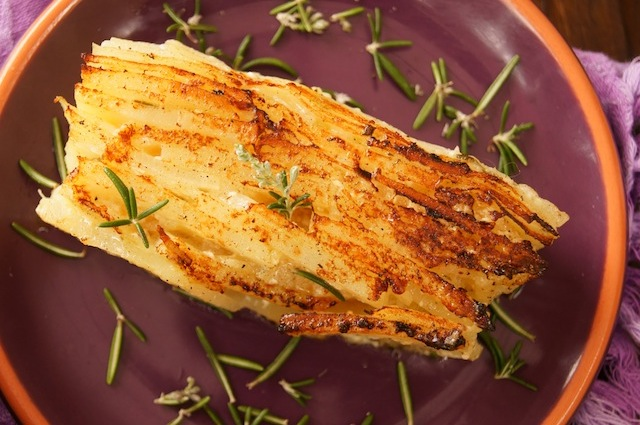 Potato Pave on a purple plate with rosemary sprigs