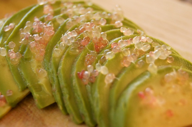 "Pink Finger Lime ""beads"" or ""bubbles"" over very thin slices of avocado."