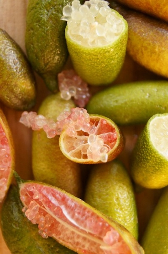 "Several Finger Limes on a cutting board, a couple are cut in half with pink ""bubbles"" of citrus juice spilling out."