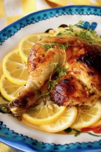 Roasted chicken thigh-leg on lemon slices with fresh thyme.