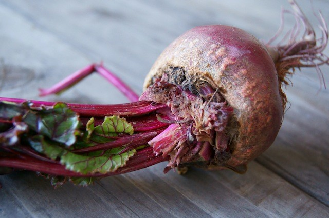 one raw beet with greens laying on it's side
