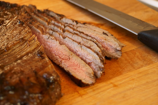 Grilled Coffee Balsamic Flank Steak, sliced into thin strip with knife on cutting board