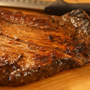 Grilled Coffee Balsamic Flank Steakon a cutting board before being sliced.