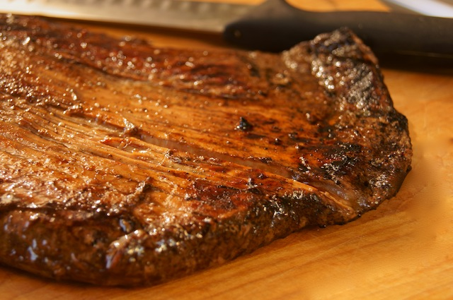 Grilled Coffee Balsamic Flank Steak in one piece on cutting board with slicing knife